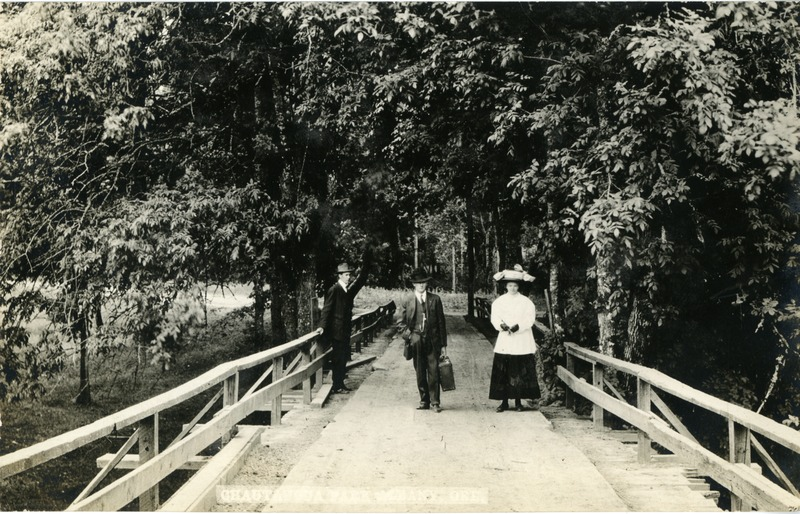 Two men and a woman stand on a bridge during the Chautauqua festival in Albany, Oregon.