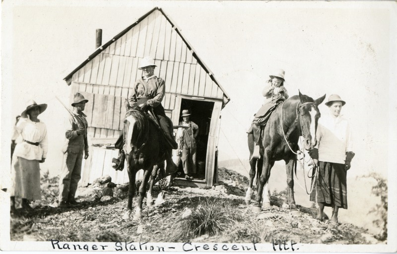 A group of people and horses at the Ranger Look-out Station on Crescent Mountain